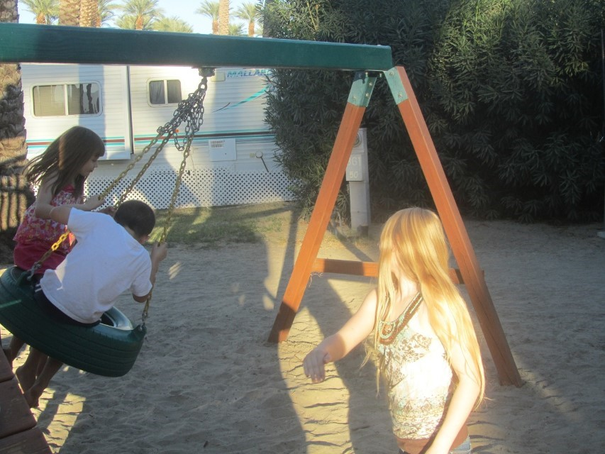Holly takes a much needed study break and pushes the kids on the swing.