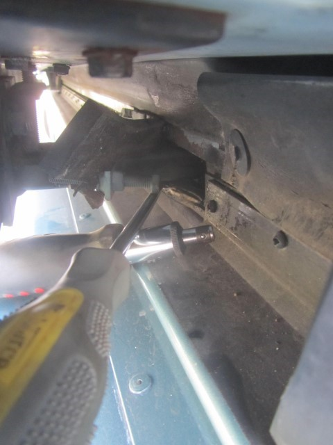 Before we get started, we have to stabilize the slide out. It is hard to see, but we are above the side door we opened, and under the slide. The screw driver is jammed in under the gear track, we put a second screw driver under it to help lift the slide up just slightly. Jam these in tight, we do not want the slide to fall when removing the gear assembly,  the slide, actually has all its weight on the gear pack. This is normally a good thing, but in this case, we need the weight removed, so we can get the gear pack out without the slide falling down. If the slide falls, you will have to lift it back into position in order to install the new gear pack.