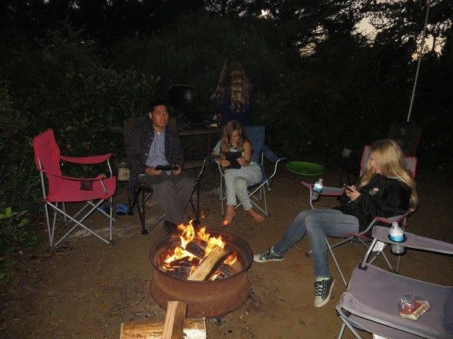 The modern campfire.  The male adult has a hand held video game thingy, The older girl is texting her John, and the younger is playing video games on the Kindle while mother makes hamburger on the BBQ in the background. I wonder if they would have noticed had I put the fire out?